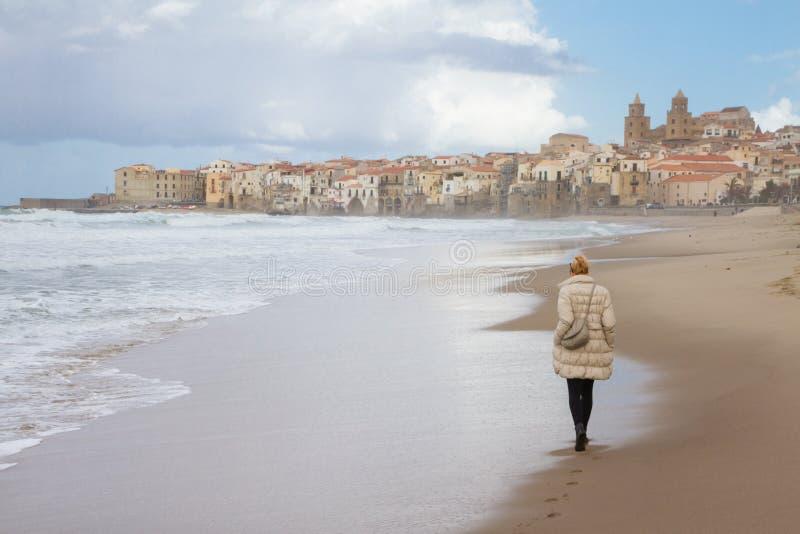 Mujer solitaria que camina la playa de Cefalu en invierno, Sicilia, Italia del sur imagen de archivo
