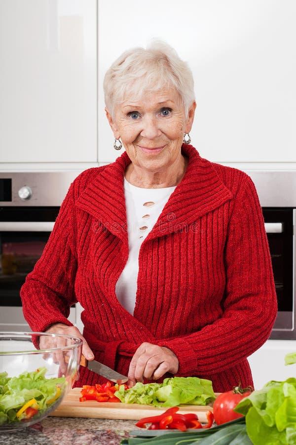 Mujer sonreída que prepara la comida imagen de archivo