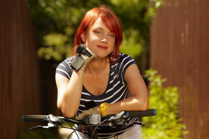 Mujer sonriente adulta joven del motorista en la bici del montaje fotografía de archivo libre de regalías
