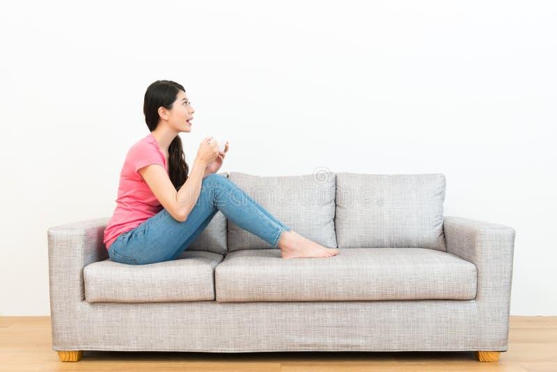 Mujer sonriente alegre que se sienta en el sofá que se relaja fotos de archivo