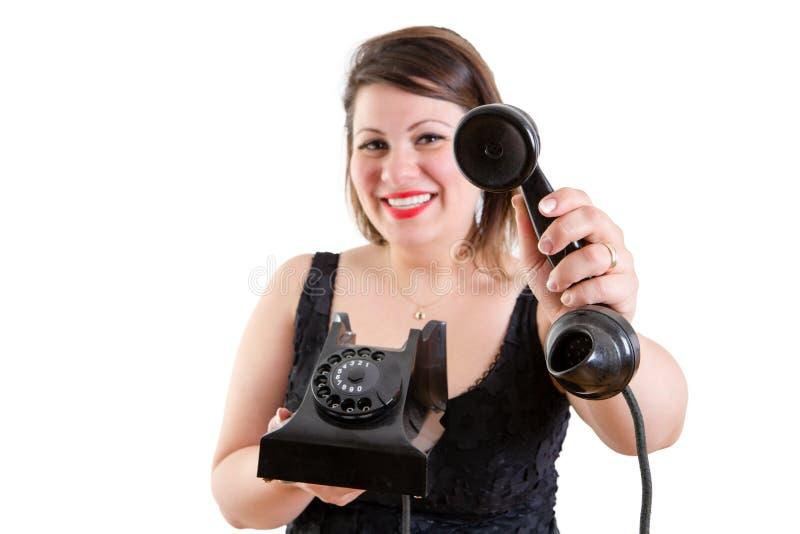 Mujer sonriente amistosa que sostiene hacia fuera un teléfono imagen de archivo