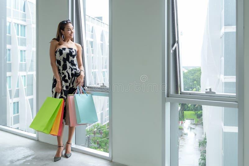 Mujer sonriente asiática de la forma de vida así que compras felices en ropa informal con los bolsos de compras en el centro come fotografía de archivo libre de regalías
