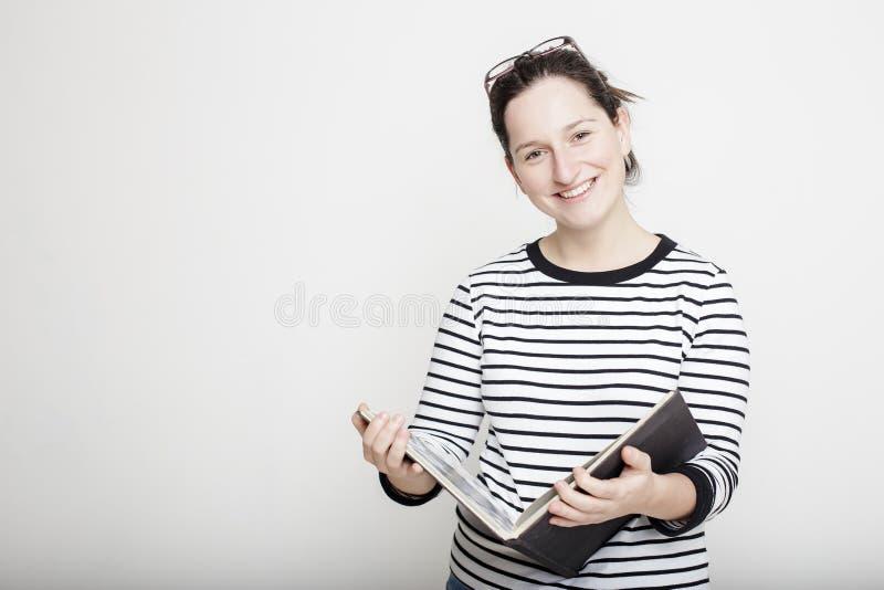 Mujer sonriente atractiva con los vidrios en su cabeza, colocándose con fotos de archivo libres de regalías
