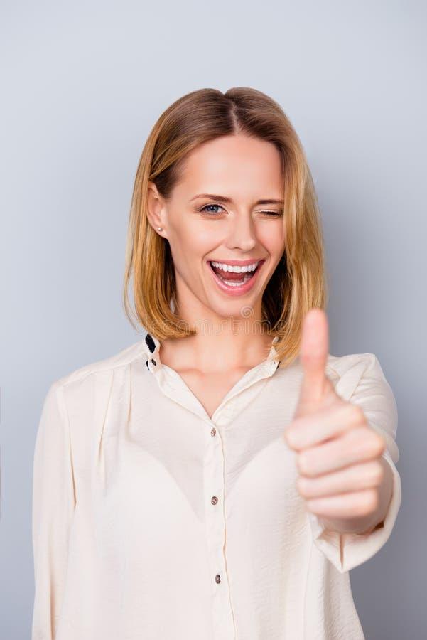 Mujer sonriente atractiva en la camisa que da un guiño y que muestra thum imagen de archivo