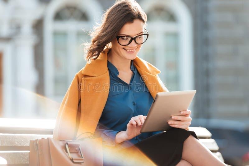 Mujer sonriente atractiva en lentes usando la tableta imágenes de archivo libres de regalías