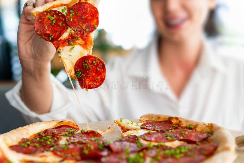 Mujer sonriente atractiva joven que come la pizza en el café de la calle Comida del tramposo Día del tramposo foto de archivo