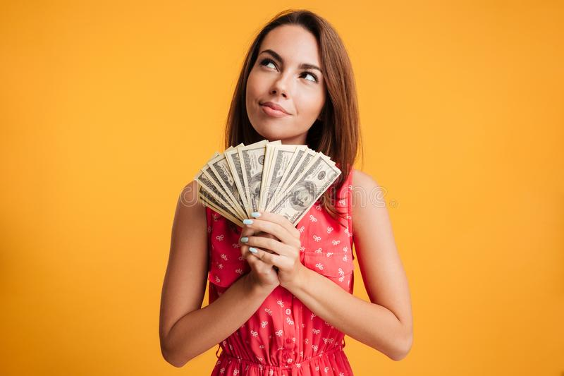 Mujer sonriente atractiva joven que piensa cómo gastar su manojo o imágenes de archivo libres de regalías