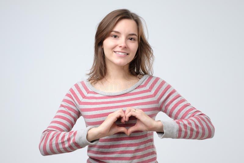 Mujer sonriente atractiva linda que muestra la muestra del corazón con sus manos imagen de archivo libre de regalías