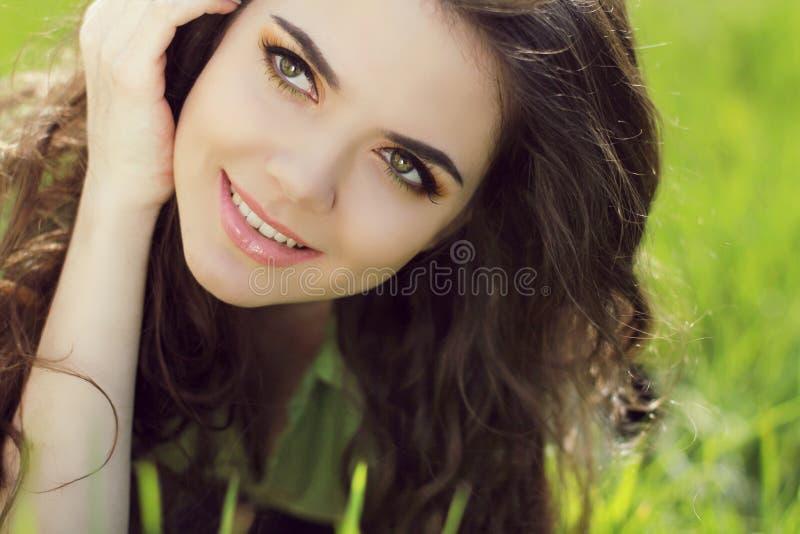 Mujer sonriente atractiva que descansa sobre la hierba verde, al aire libre portra foto de archivo libre de regalías