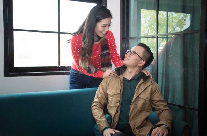 Mujer sonriente atractiva que se coloca con su marido que mira para arriba cariñosamente en sus ojos imagen de archivo
