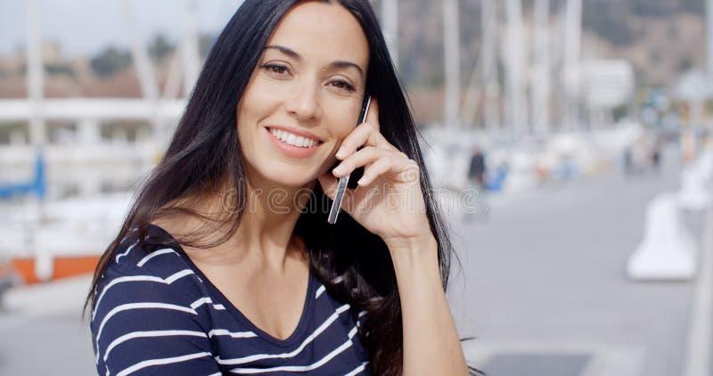 Mujer sonriente atractiva que usa un teléfono móvil foto de archivo libre de regalías