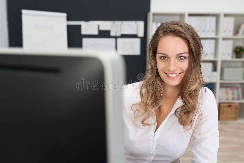 Mujer sonriente bonita de la oficina que mira la cámara fotografía de archivo libre de regalías