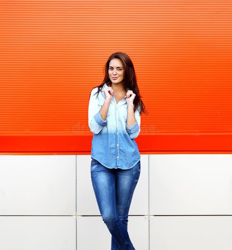 Mujer sonriente bonita elegante que presenta contra la pared colorida fotografía de archivo