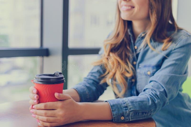 Mujer sonriente bonita que se sienta cerca de la ventana en un café en la ropa informal que bebe el café sabroso fresco y que tie fotos de archivo libres de regalías