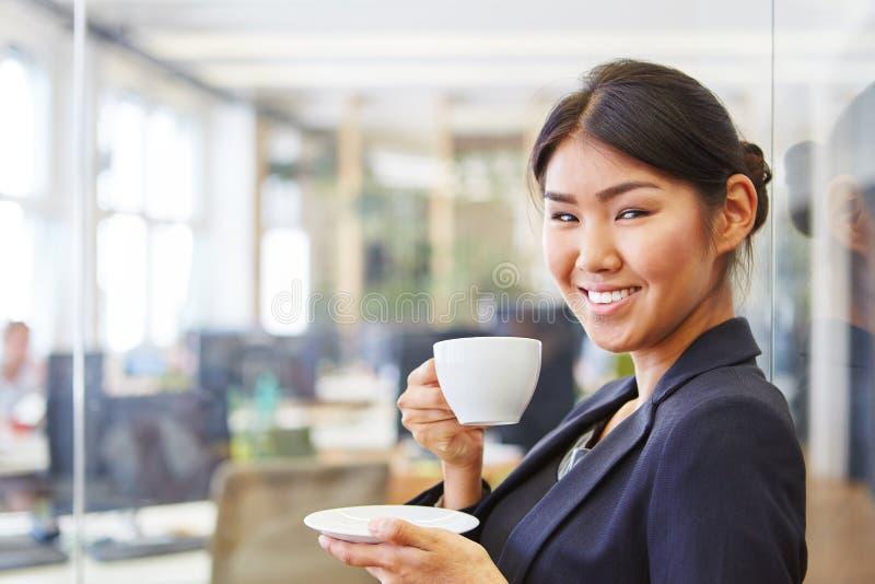Mujer sonriente como empresaria que toma un descanso para tomar café imagenes de archivo