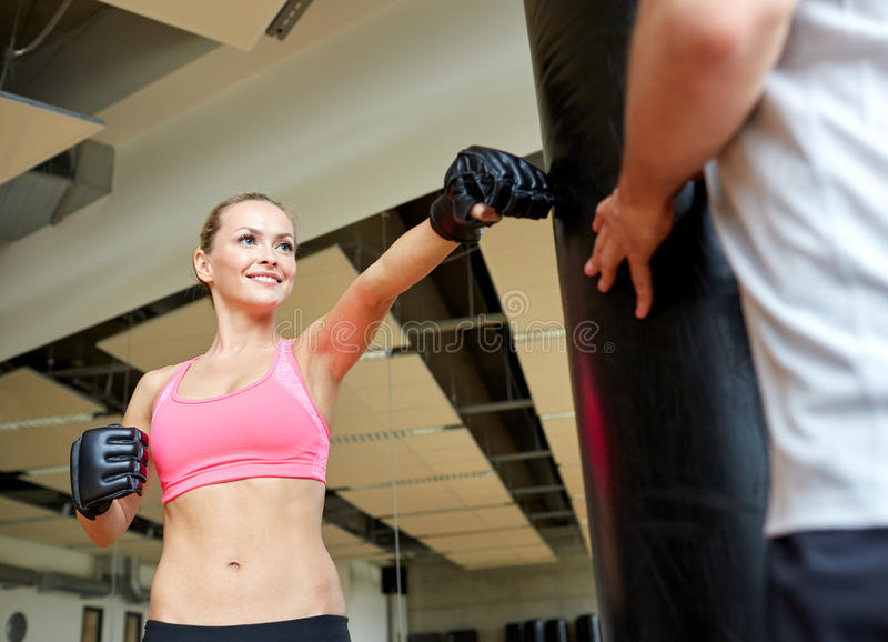 Mujer sonriente con el boxeo personal del instructor en gimnasio fotografía de archivo libre de regalías