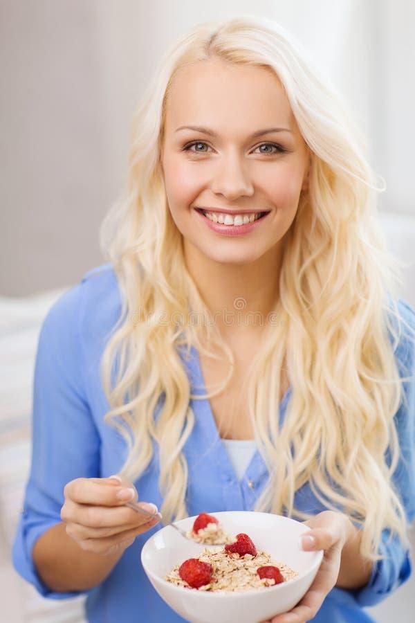 Mujer sonriente con el cuenco de muesli que desayuna fotos de archivo