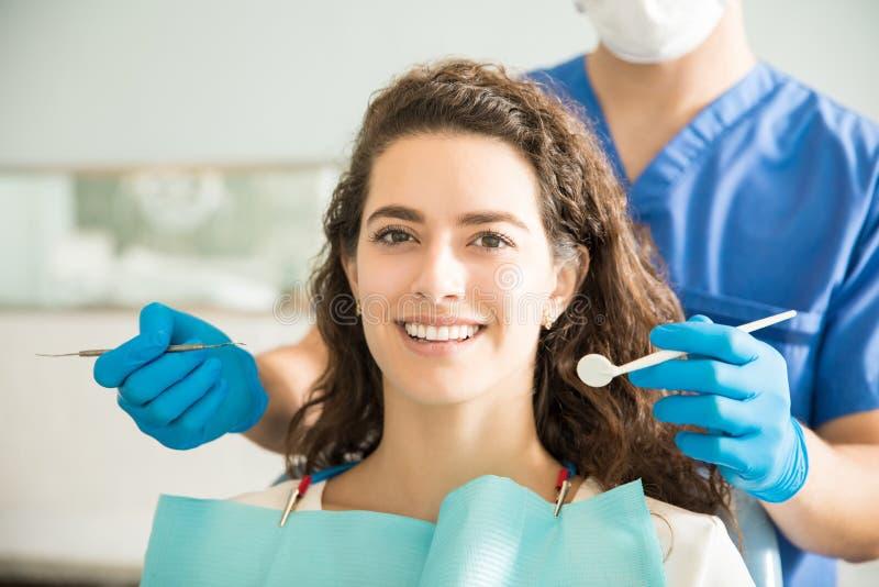 Mujer sonriente con el dentista Holding Dental Tools en la clínica imagen de archivo libre de regalías