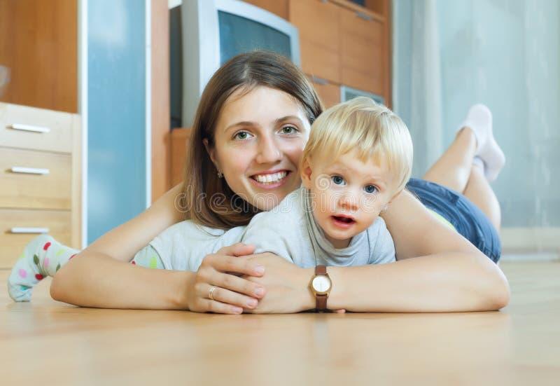 Mujer sonriente con el niño en piso de madera imagenes de archivo