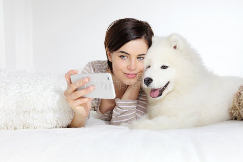 Mujer sonriente con el perro casero Selfie fotografía de archivo