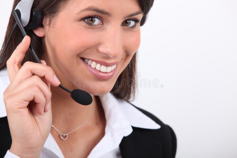 Mujer sonriente con el receptor de cabeza foto de archivo