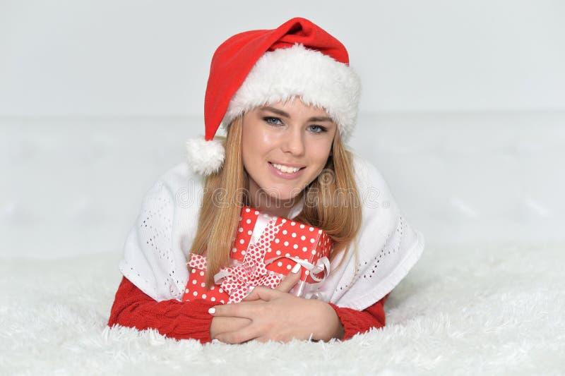 Mujer sonriente con el regalo de la Navidad en casa fotografía de archivo libre de regalías