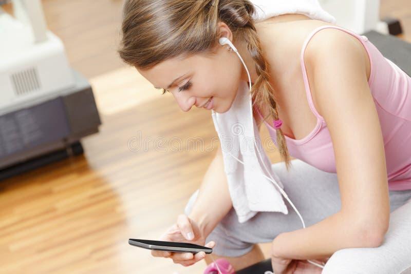 Mujer sonriente con el teléfono elegante en el gimnasio imagen de archivo libre de regalías