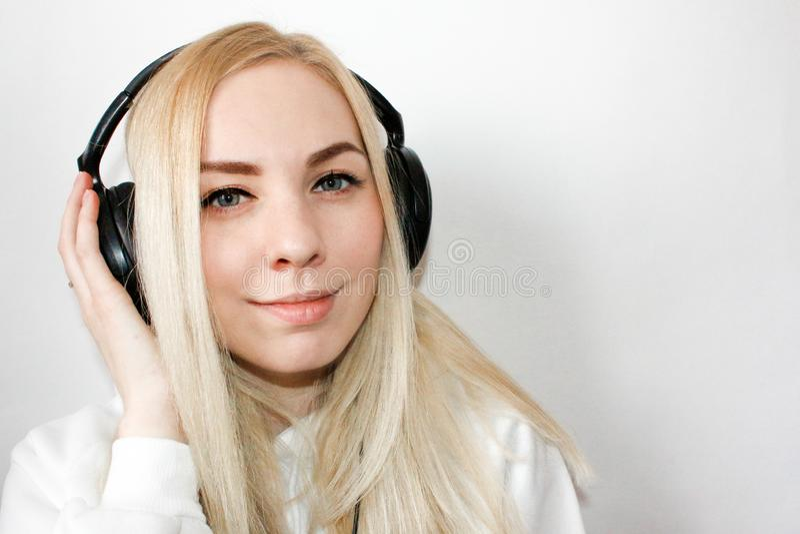 Mujer sonriente con en los auriculares que escucha la música en el fondo blanco, visión superior Modelo divertido atractivo en vi fotografía de archivo libre de regalías