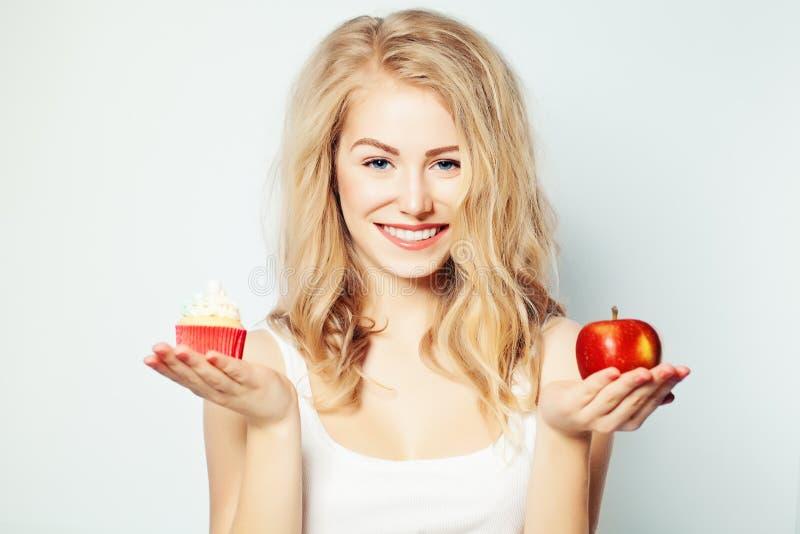 Mujer sonriente con la comida sana y malsana foto de archivo