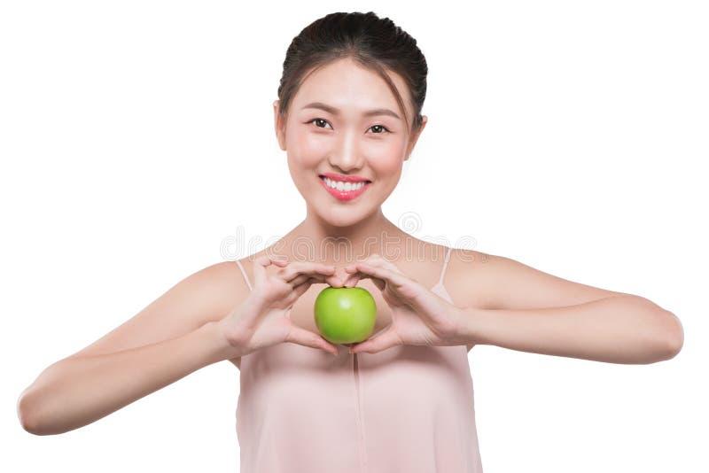 Mujer sonriente con la piel sana que sostiene la manzana verde imagen de archivo libre de regalías