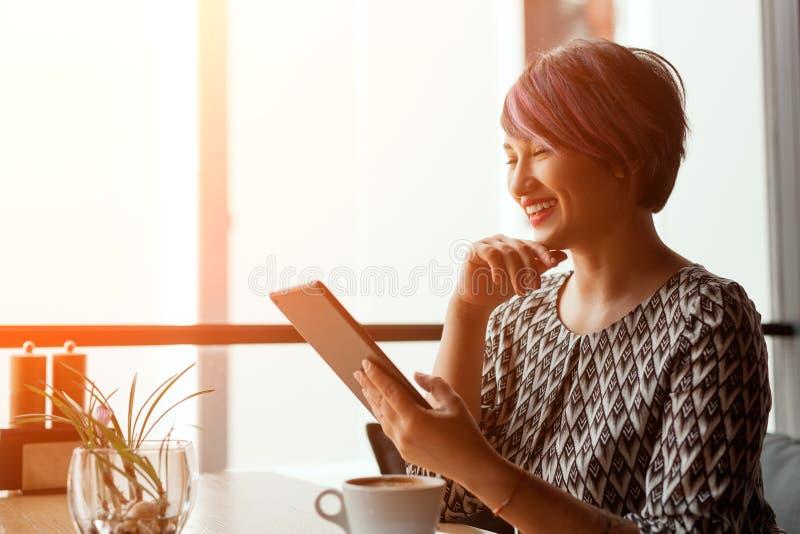 Mujer sonriente con la tableta en café imagen de archivo