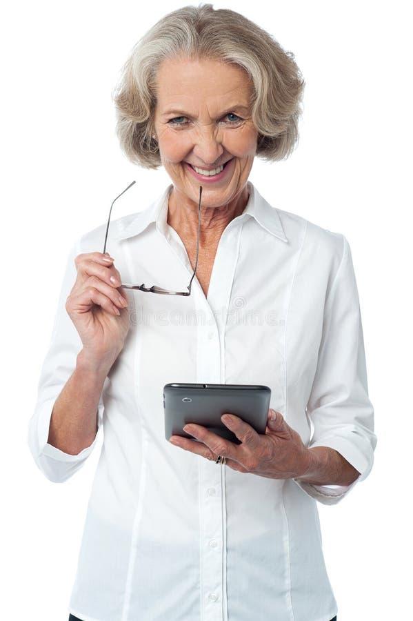 Mujer sonriente con la tableta sobre blanco imagen de archivo libre de regalías