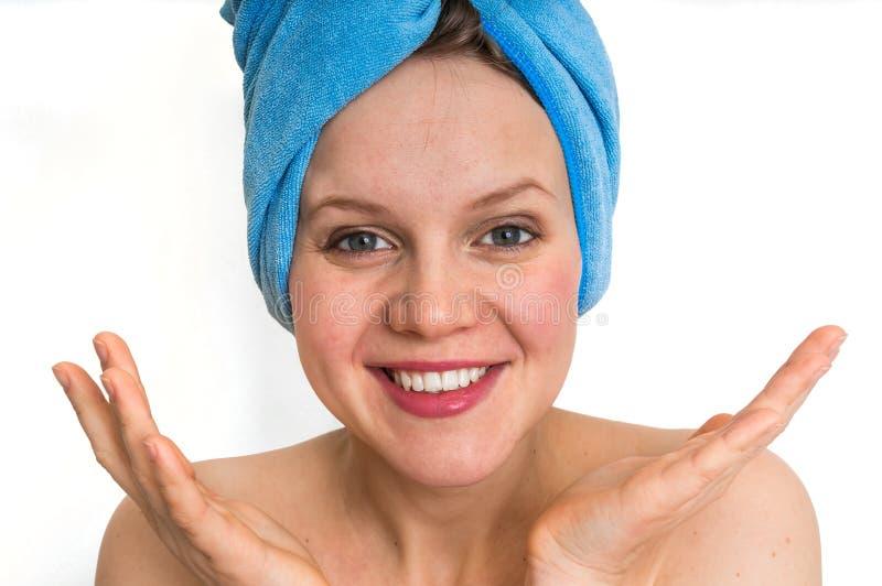 Mujer sonriente con la toalla azul en su cabeza aislada en blanco fotos de archivo