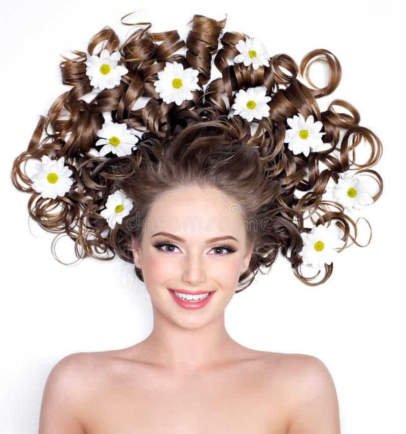 Mujer sonriente con las flores en pelo fotos de archivo libres de regalías