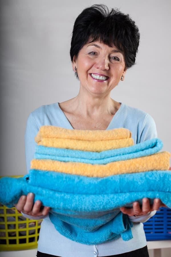 Mujer sonriente con las toallas imagen de archivo libre de regalías