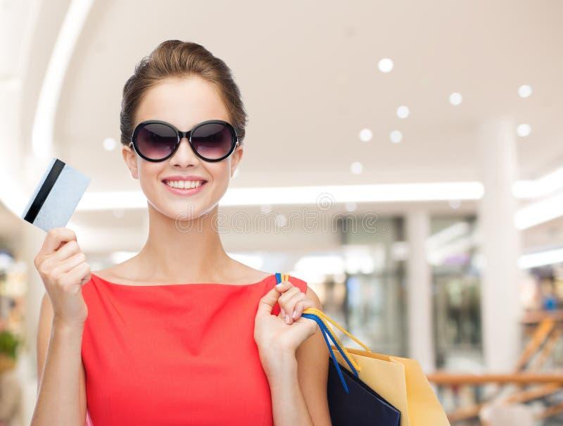 Mujer sonriente con los bolsos de compras y la tarjeta de crédito fotografía de archivo