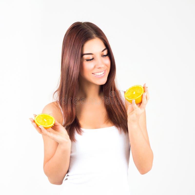 Mujer sonriente con los dientes blancos que sostienen dos halfs de naranja La mujer mira la naranja Alimento de Healty imagen de archivo