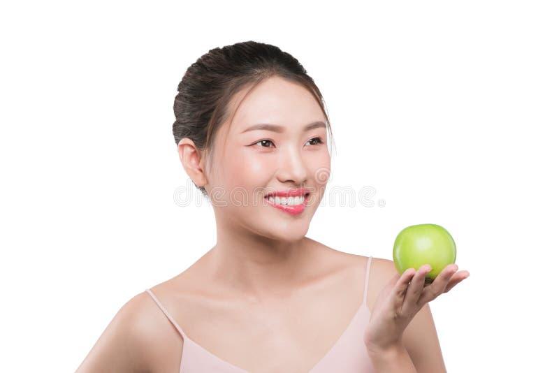 Mujer sonriente con los dientes sanos que sostienen la manzana verde fotos de archivo libres de regalías