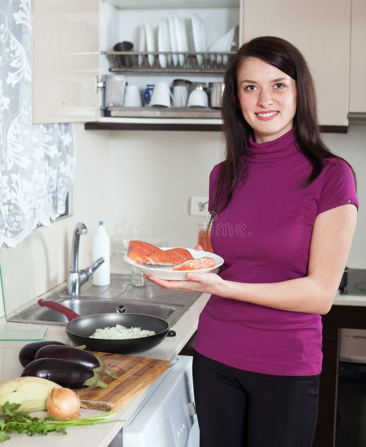 Mujer sonriente con los pescados de color salmón crudos con las verduras imagenes de archivo