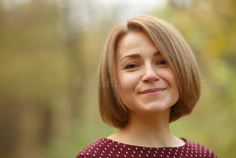 Mujer sonriente con maquillaje natural y corte de pelo de moda al aire libre imagenes de archivo