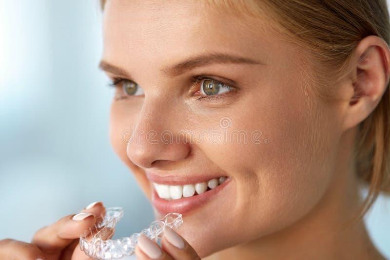 Mujer sonriente con sonrisa hermosa usando instructor invisible de los dientes fotos de archivo