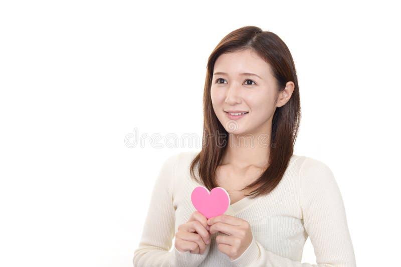 Mujer sonriente con un coraz?n rosado fotografía de archivo
