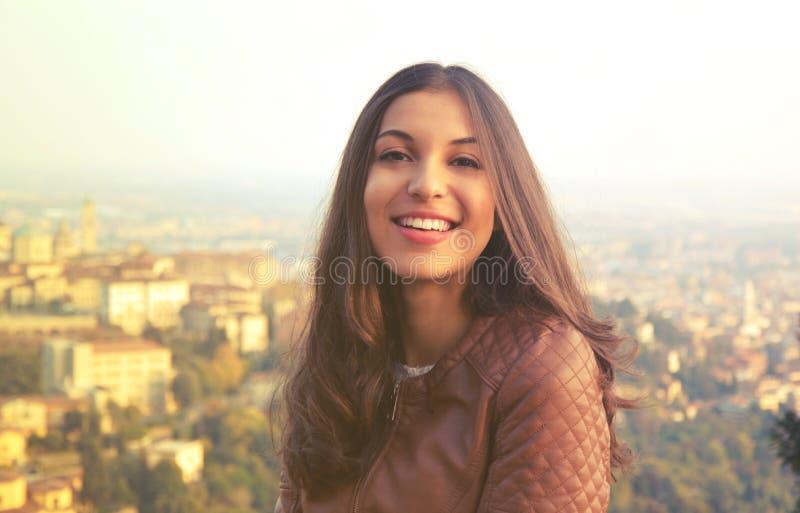 Mujer sonriente confiada joven que mira la cámara al aire libre en la puesta del sol fotos de archivo