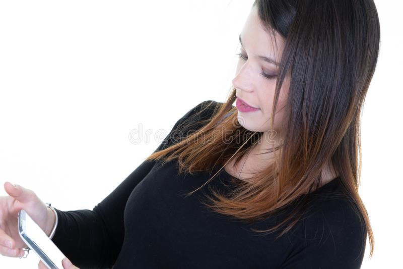 Mujer sonriente de la belleza joven que manda un SMS usando el teléfono móvil contra el fondo blanco imagen de archivo libre de regalías
