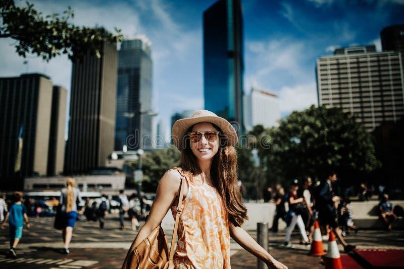 Mujer sonriente de la cara en sombrero y gafas de sol que explora la ciudad, con el horizonte de Sydney en el fondo imagenes de archivo