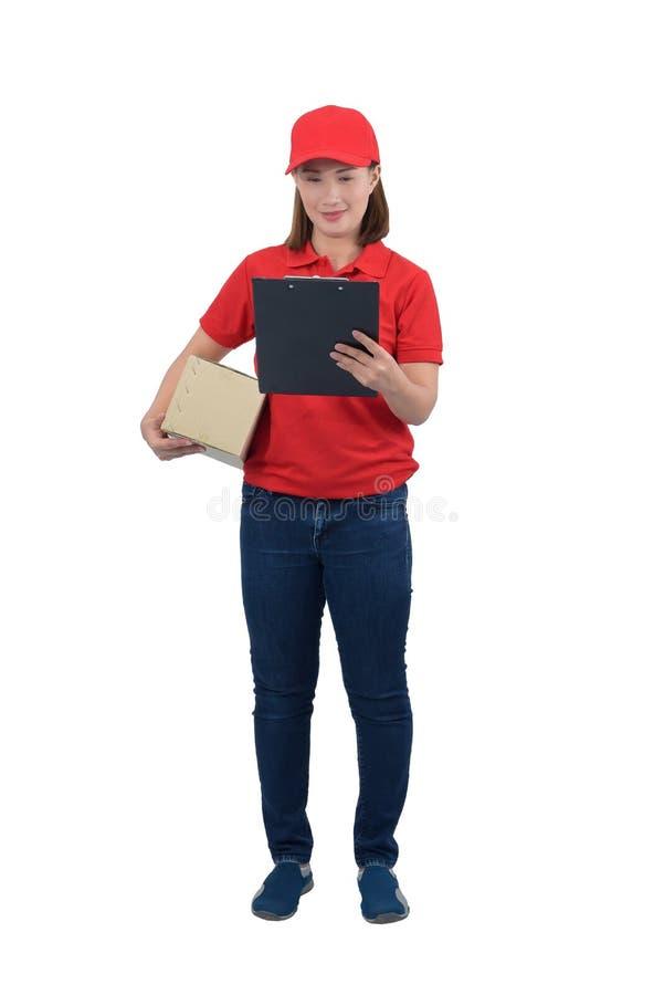 Mujer sonriente de la entrega en el uniforme rojo que da las cajas y el tablero del paquete, aislados en el fondo blanco imágenes de archivo libres de regalías