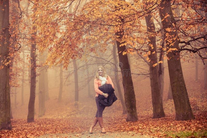Mujer sonriente de la moda con la chaqueta en parque imagenes de archivo