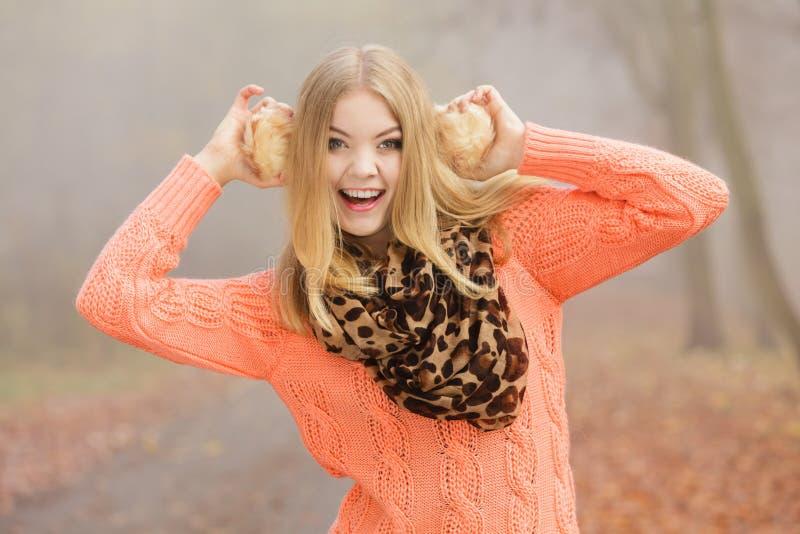 Mujer sonriente de la moda en el parque que sostiene orejeras fotografía de archivo