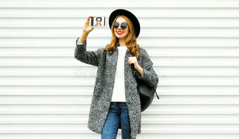 Mujer sonriente de la moda que toma el selfie por smartphone en capa gris imagenes de archivo
