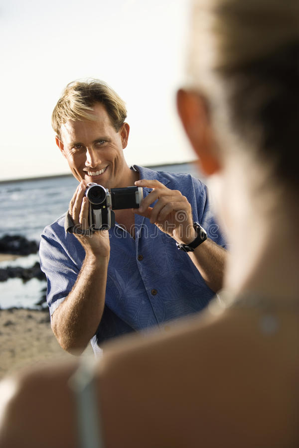 Mujer sonriente de la película del hombre en la playa foto de archivo libre de regalías